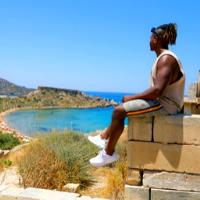 Man sitting on a walk near a beach