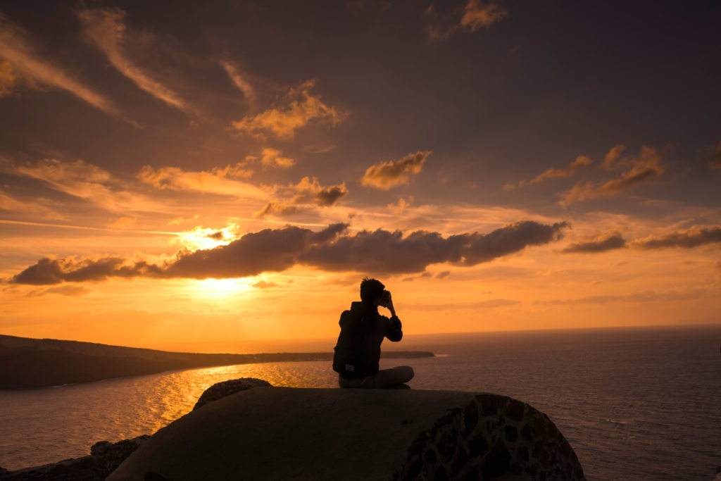 A backpacker sitting on a rock in Santorini during sunset