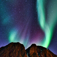 Northern lights above two mountains
