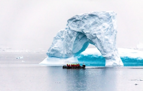 Hurtigruten boat with passengers passing an ice arch