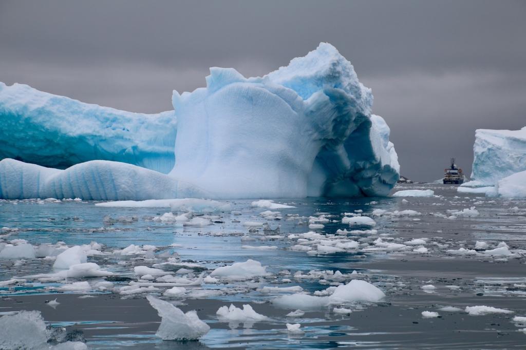 Boat passing through icy landforms in Antarctica