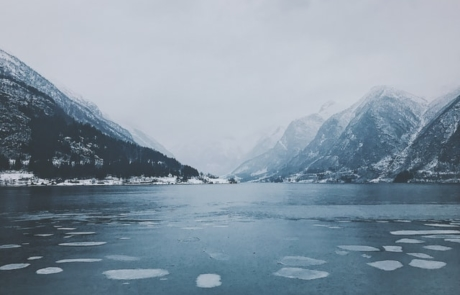 Image just above the water looking st icy and snowy mountains
