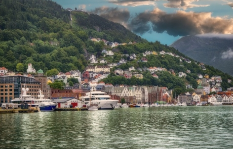 Water way in Bergen with building on the hill and boats on the water