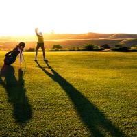 Person swinging a golf club on a fairway