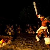 Zulu man dancing around a fire