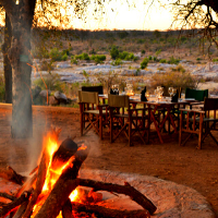 Campe fire with a wooden table and chairs in the background