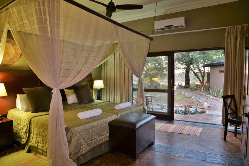 A lodge room with draping over the bed