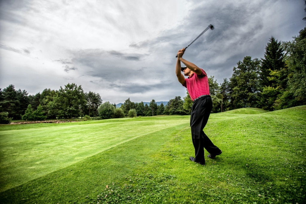 Left handed golfer swinging on the course