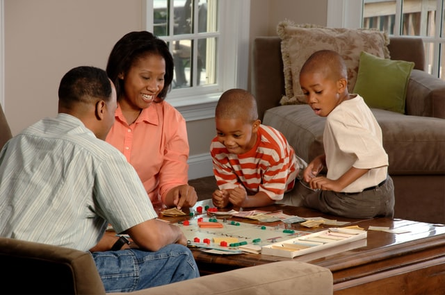 Family playing a board game at a coffee table