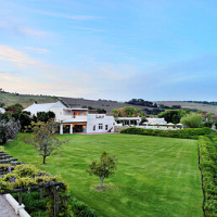 View of a white building with lush green follage around it