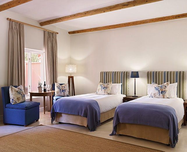 Twin bedroom of a hotel with a blue finish