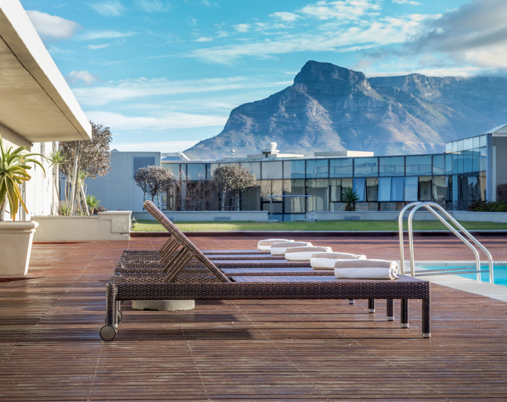 Pool chairs by a hotel pool with a mountain in the backdrop