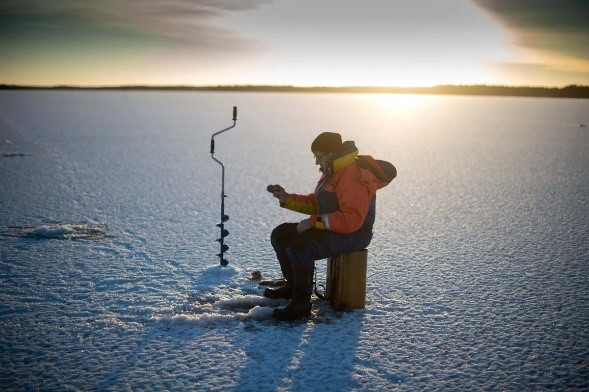 A man sitting on ice busy ice fishing